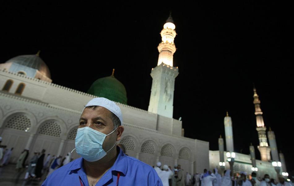 12. Мусульманский паломник в маске против вируса H1N1 идет по двору мечети пророка Мухаммеда в святом городе Медина 11 ноября 2009 года. (MAHMUD HAMS/AFP/Getty Images)