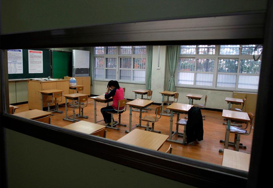 22. Студентка из Южной Кореи с высокой температурой была помещена в отдельный класс в целях предосторожности перед началом вступительного экзамена в Тэджоне к югу от Сеула, Южная Корея, в четверг 12 ноября 2009 года. (AP Photo/Yonhap, Yang Yong-suk)
