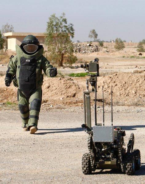 Иракский солдат с роботом, помогающим в разминировании