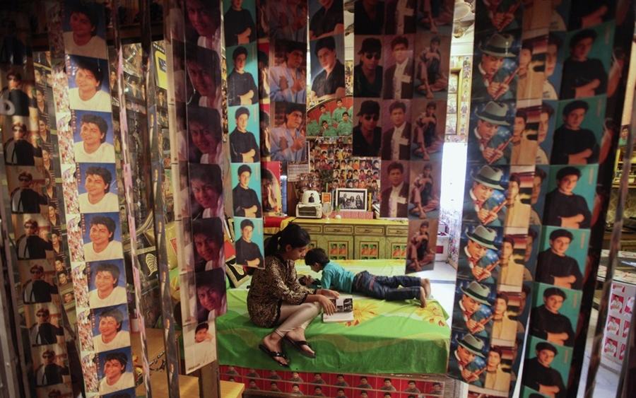 Дети бизнесмена в своей комнате, которую их отец украсил фотографиями Шах Рух Хана