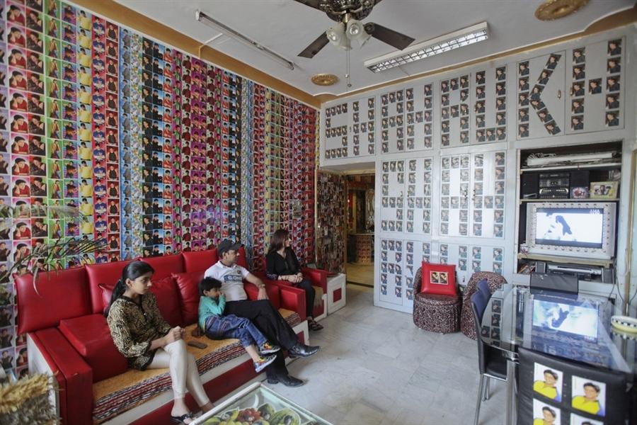 Вишал Сингх с женой и детьми смотрят телевизор, который так же отделан фотографиями актера