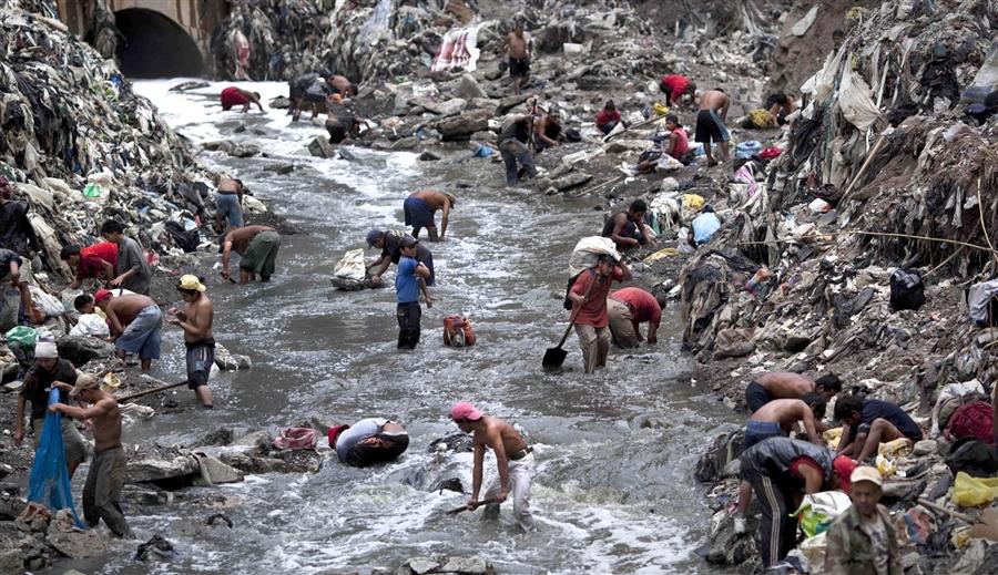 Поиск металла на дне мусорной канавы в Гватемале