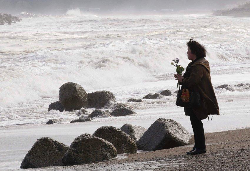 Люди приносят цветы на побережье