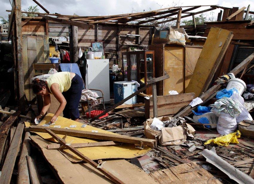 Женщина ищет личные вещи под обломками своего дома