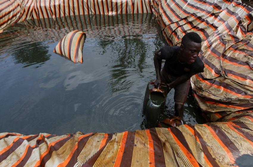 Сырая нефть хранится в искусственно сделанном бассейне, её наливают в канистры вручную.