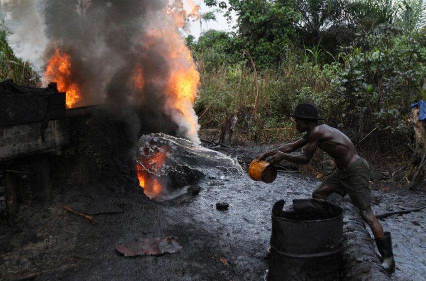 Рабочий льет воду в огонь, чтобы охладить нефть, вдыхая при этом ядовитые пары.