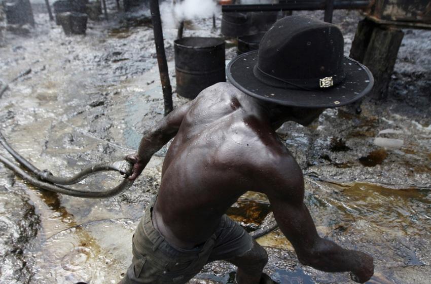 Рабочий несет шланг, чтобы откачивать сырую нефть